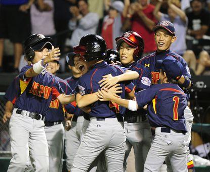 Japan teammates celebrate after scoring the winning run in Saturday's Cal Ripken World Series International Championship game.