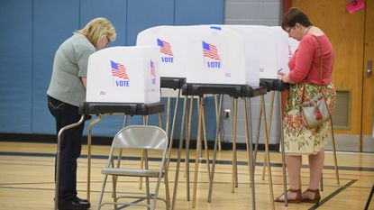 A pair of voters fill out their ballots in voting stalls at Elkridge Elementary School on primary election day, Tuesday, June 26.