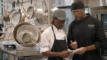 Chef Roman Walker, right, explains the dating process for foods to prep cook Eddie Terrill at Humanin Culinary Social Enterprise kitchen in the City Seeds building.