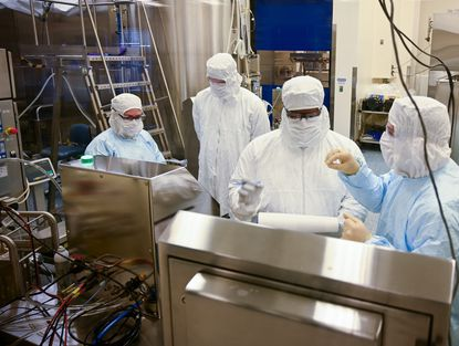 Manufacturing associates work on a COVID-19 vaccine in one of four flexible manufacturing suites at Emergent BioSolutions' Bayview facility. (Jerry Jackson/Baltimore Sun)