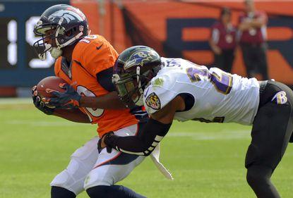 Ravens cornerback Jimmy Smith stops Denver Broncos wide receiver Emmanuel Sanders (10) after a pass reception.