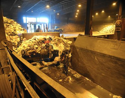 A loader drops a bucket of trash into one the Harford County waste-to-energy facility's furnaces Monday. The plant is closing this week after 29 years.