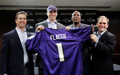 Baltimore Ravens first round draft pick, quarterback Joe Flacco, holding jersey, is surrounded by members of the team's staff, coach John Harbaugh, far left, general manager Ozzie Newsome, right, and director of college scouting Eric DeCosta, far right, during a news conference, Sunday, April 27, 2008, in Owings Mills.