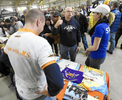 Gary Bernstein, center, of Reisterstown, talks with Mike Tomlin, left, and Courtney Baltimore, right, at a Bike MS table during Sunday's Stop Swap and Shop bike expo at the Carroll County Agriculture Center in Westminster Sunday, Jan. 8, 2015. Tomlin and Baltimore were registering riders for this summer's Bike MS: Chesapeake Challenge, a two day ride benefitting the National Multiple Sclerosis Society.