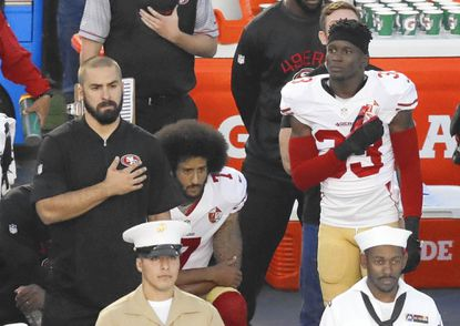 FILE - In this Thursday, Sept. 1, 2016 file photo, San Francisco 49ers quarterback Colin Kaepernick, middle, kneels during the national anthem before the team's NFL preseason football game against the San Diego Chargers, in San Diego. The Santa Clara police chief has vowed to continue providing a safe environment at San Francisco home games after the union representing his officers threatened to boycott policing the stadium if the 49ers don't discipline Kaepernick for criticizing police and refusing to stand during the national anthem. Chief Michael Sellers said in a statement Saturday, Sept. 3, 2016, that he will urge union leadership to put citizens' safety first. (AP Photo/Chris Carlson, File)