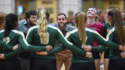 Century head coach Bryan Trumbo, center, talks to his team as they celebrate their win over Rising Sun in a 2A semifinal match during the MPSSAA State Volleyball Tournament at University of Maryland's Ritchie Coliseum on Wednesday, November 13.