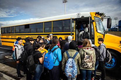Students board an electric school bus in Sacramento, California on December 18, 2019. The Twin Rivers School District uses 25 electric school buses built by Lion Electric. (Max Whittaker/The New York Times)
