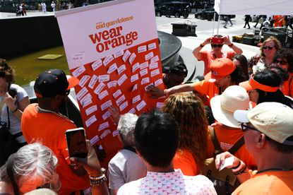 Demonstrators post the names of loved ones who have died by gun violence ata Wear Orange rally in New York in 2019. The annual event takes place throughout the country each year to bring awareness to efforts to end gun violence.