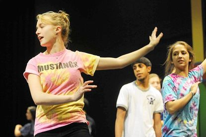 """Marriotts Ridge junior Maddie Rodrigue, left, leads Charith Ranawake and Brynn Morales, right, and other members of the the cast through a portion of a dance she choreographed for """"Jukebox."""""""
