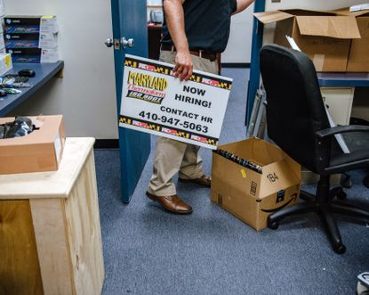 """Matthew Livesay with a """"Now Hiring"""" sign at Maryland Thermoform in Baltimore last year as the company tried to hire people as entry-level machine operators or warehouse workers, paying $12 to $15 an hour. (Andrew Mangum/The New York Times)"""