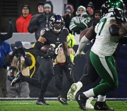 The Ravens' Chuck Clark, left, runs back an interception against the Jets in the second quarter last season.