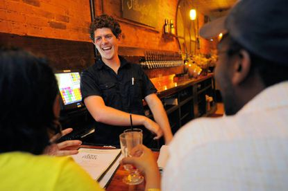 Bartender Ryan Travers chats with patrons Neemisha Mufuka (left) and her husband, Tendai, at Of Love and Regret.