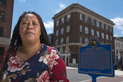A newly erected plaque memorializing the three lynching victims stand on the street corner behind La'Tanya Christopher, who stands in front of the old Salisbury courthouse, the site of condoned lynchings including Garfield King, related to the courthouse employee Thu., May 27, 2021. (Karl Merton Ferron/Baltimore Sun)