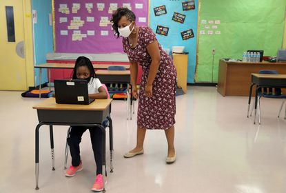 Second-grader Jacqueline Solano gets instructions from her teacher Tiffany Harmon during first day of face-to-face eLearning at Broward Estates Elementary School in Lauderhill Florida on Friday, October 9, 2020. (Mike Stocker/South Florida Sun Sentinel)
