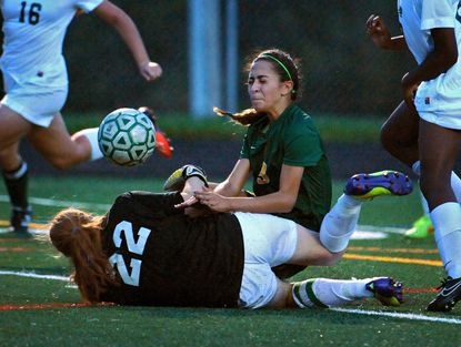 Wilde Lake's Sahar Zoghi, right, battles for the ball against Atholton goalie Sage Mayhew in the first half.