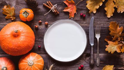 Autumn or thanksgiving day table setting. Fallen leaves, pumpkins, spices, empty plate and vintage cutlery on wooden table.
