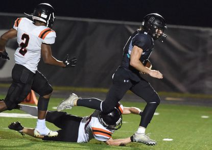 Patterson Mill quarterback Thomas Rohal avoids being tripped up by Rising Sun's Sam Erhart and Jeremy Flowers, left, as he sprints ahead for a third quarter touchdown during a football game at Patterson Mill High School on Friday, Sept. 17, 2021.