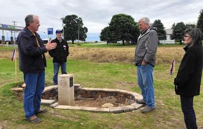 Pat Simon, left, a Maryland surveyor and Harford County resident, talks about Crown Stone 40 after a dedication ceremony for the replica shown here. Crown Stone 40 marks the 40th mile of the Mason-Dixon Line in northern Harford County.