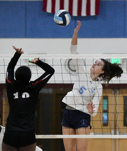 On right, Mary Grace Goyena, Mount de Sales, hits the ball over Kayla Cook, Archbishop Spalding, in the third game of their high school volleyball match on October 1, 2019.