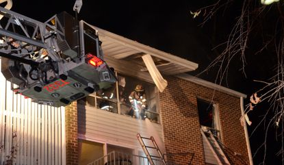 A firefighter sprays water around an apartment unit in Bel Air that was gutted by a fire Thursday night.