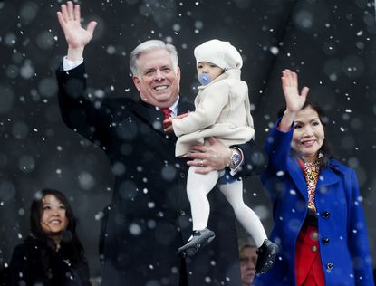Governor Larry Hogan waves to the crowd and holds his granddaughter Daniella Valez, 2, with first lady Yumi Hogan, at the close of his inauguration in Annapolis.
