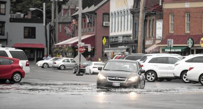 A motorist slowly navigates through remaining water from the higher-than-normal tide in downtown Annapolis. Baltimore and Annapolis had a record 12 days each of nuisance flooding in 2018.