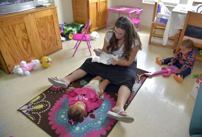 Tabatha Pettigrew, a resident at the Dayspring transitional housing program, changes her daughter, Arionna Pettigrew's diapers as her youngest child, Nelson Pettigrew, 1, plays at right.