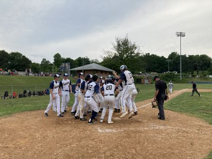 Catonsville senior Nick Eiswert, center (7), steps on home plate with both feet as Aidan Callinan (17), Eli Beyer (20) and Daniel Capka (22) and the rest of the Comets await the celebration after his walk-off home run.