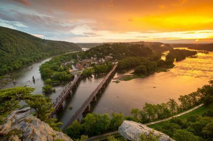 MARC commuter trains cross the confluence of the Potomac and Shenandoah rivers to enter Harpers Ferry, West Virginia. But the town is one of several in the state facing a loss of two-thirds of its commuter rail service unless West Virginia officials come up with $2 million to cover operating costs.