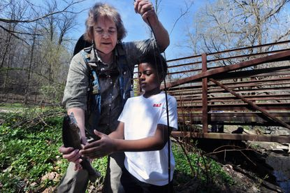 Volunteer guild Norma Hayes, left, of Towson, helps Jabari Lyles, 8, of Baltimore, handles a trout he caught. Maryland Trout Unlimited hosted about 70 kids and their families on its annual City Catch at Leakin Park. The group provided fishing rods and guides to teach them fishing techniques and instill some sense of conservation ethic.