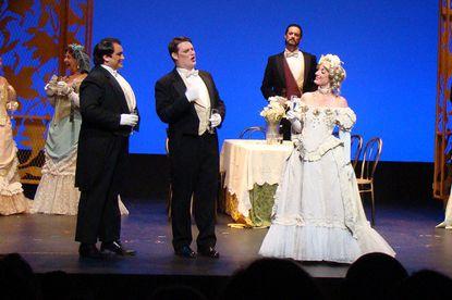 "From left, actors Peter Scott Drackley (Alfredo), Andrew Etherington (Gaston de Letorieres), Peter Tomaszewski (Baron Douphol) and Joy Greene (Violetta) perform during Act 1 of Opera AACC's production of ""La Traviata."""