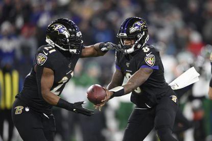 Baltimore Ravens quarterback Lamar Jackson (8) hands off to running back Mark Ingram (21) during the first half of an NFL football game against the New York Jets in Baltimore.
