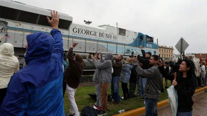 People wave at a train that is carrying the casket of former U.S. President George H.W. Bush to the George H.W. Bush Presidential Library at Texas A&M University on December 6, 2018 in Navasota, Texas.
