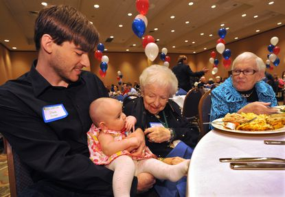 Steve Gruber, of Pasadena, holds his daughter Isla Rose Gruber, 4 1/2 months, so that Rose Rosenfield, 92, of Owings Mills, can meet her. Rosenfield's sister Micki Naiditch, 85, looks on. More than 160 descendants of the Hankin family, who first came to Baltimore in 1912, gathered for a centennial celebration at a Pikesville hotel.
