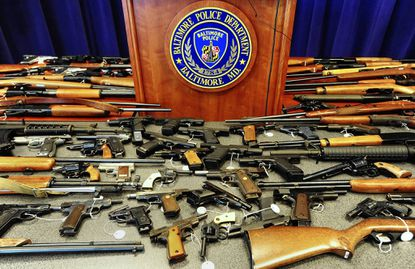 Baltimore police display more than 70 illegal firearms that they seized over the course of a single summer. File.