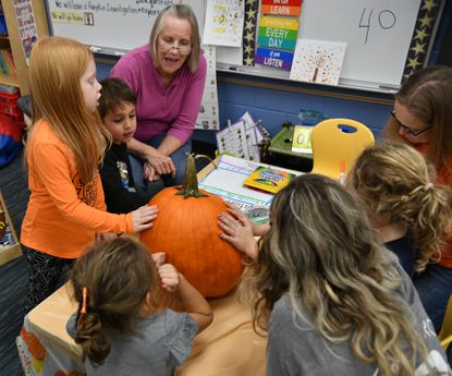 A group of Red Pump Elementary School Kindergartners and parent volunteers talk about the large pumpkin in front of them as they participate in the Pumpkin Investigation Learn with Me lesson at Red Pump Elementary School on Oct. 31. Learn With Me events are designed for families to become part of the teaching and learning experience, school officials said, and will replace the traditional visitation during American Education Week this year.