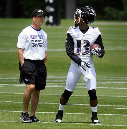 Ravens coach John Harbaugh, left, talks with cornerback Aaron Ross, right, during the second day of mandatory minicamp.