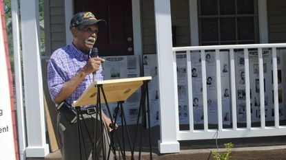 Louis Diggs, a local historian, speaks in the Winters Lane community about the area's history during a ceremony for the completion of affordable renting units.