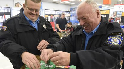 Kenny Carlisle and Larry Myers volunteer preparing tags for the Shop with a Cop Angel Tree at Walmart in Westminster on November 21, 2018.