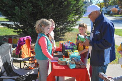 Anthony Ravello, of Arbutus, buys cookies from Halethorpe area Girl Scouts outside the Halethorpe Elementary School polling center during the 2016 General Election.