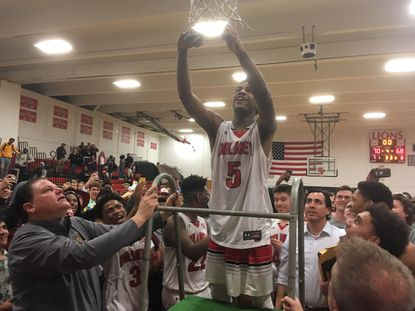 Dulaney sophomore Ryan Conway cuts down the net after he netted 30 points in the Lions' 70-68 win over Springbrook in the Class 4A North Region championship game.