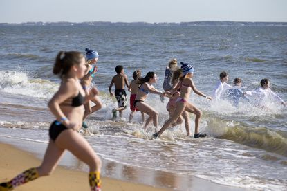 Plungers run into the water during the Pee Wee Plunge at the 2018 MSP Polar Bear Plunge in Sandy Point State Park in Annapolis.