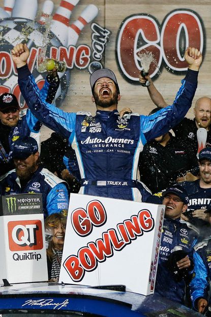 Martin Truex Jr., driver of the No. 78 Auto-Owners Insurance Toyota, celebrates in Victory Lane after winning the Monster Energy NASCAR Cup Series Go Bowling 400 at Kansas Speedway.