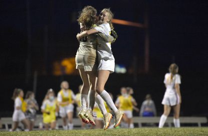 Century girls soccer teammates Amelia Graff and Jane Brewer jump into each others arms to celebrate their 2-0 win over host Liberty on April 13.