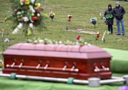 "Guest mourn while keeping a six-foot social distance during the funeral of Norbert Coyne McDermott III, better known as ""Bert,"" amid the COVID-19 pandemic on Saturday, March 21, 2020, at Mt. Royal Cemetery in Shaler, Pa."