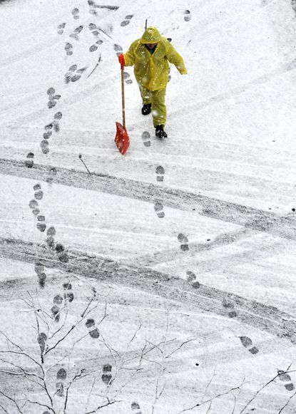 Efrain Chicas walks through accumulating snow on the roadway while clearing walkways outside Carroll Hospital Center in Westminster.