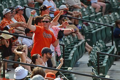 Fans dance to music as a pitcher warms up during a game in which the Orioles hosted the White Sox at Oriole Park at Camden Yards. July 11, 2021. (Kim Hairston/Baltimore Sun).