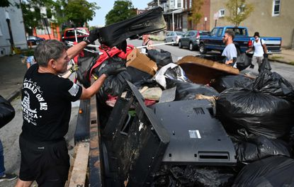 Volunteers fill a flatbed trailer with trash collected from alleys near Fulton Ave Monday morning. They were inspired to come out and help by Scott Presler, a Republican activist who organized the cleanup via Twitter.