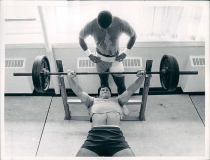 Former Colts middle linebacker Ed Simonini on the bench press while Glenn Howard spots him.
