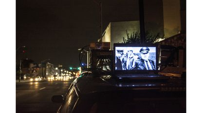 A laptop and projector on top of a car near the Eastern District Courthouse for Shorty and Brian's Dinner and a Movie.